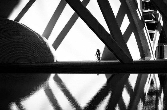 A cyclist passes through the City of Arts and Sciences of Valencia