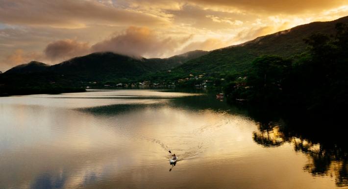 Aerial image of a woman doing kayak in Lagoa da Conceição, Florianopolis, Brazil.
