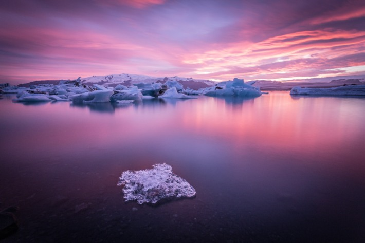 A stunning sunset colors the floating icebergs of the Jokulsarlon Glacier Lagoon in Iceland. It was a cloudy day so this amazing sunset has been unpredictable, but once we were there, it's been like living in a dream.