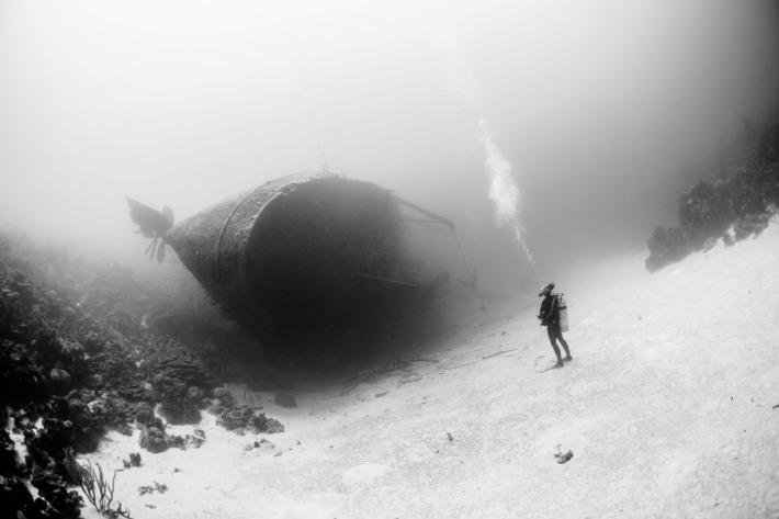 A diver stand up front of the Hilma Hooker wreck. He look this boat and seem think it will never go away...it is sure.  Also the bubbles seem make an interrogation point. The Hilma Hooker is a 200ft boat wreck. It rests with 100ft of water in the Caribbean Sea in Bonaire (a famous destination for scubadiving).